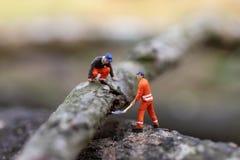Miniatuurmensen: Registreerapparaat houten knipsel voor huisbouw, die beeld voor bedrijfsconcept gebruiken royalty-vrije stock afbeeldingen