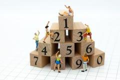 Miniatuurmensen: Reiziger die aan stapel van aantal houten blok beklimmen Beeldgebruik voor gezond, oefeningsconcept stock afbeelding