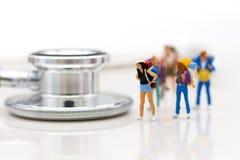 Miniatuurmensen: Reizigers met de controles van de pre-vertrekgezondheid Beeldgebruik voor gezond, reisconcept royalty-vrije stock fotografie
