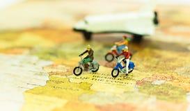 Miniatuurmensen, reizigers met fiets op wereldkaart, die aan bestemming cyling Royalty-vrije Stock Foto