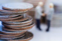 Miniatuurmensen: Twee zakenlieden maken tot een overeenkomst, met stapel muntstukken aan achtergrond, gebruikend als verplichting Stock Foto's