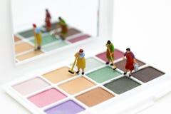 Miniatuurmensen: Vrouwen die hulpmiddelen, oogschaduw schoonmaken Beeldgebruik voor de schoonheid, cosmetische product stock afbeelding