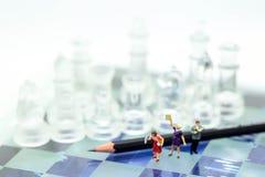Miniatuurmensen: Zakenman die een boek met potlood en CH lezen royalty-vrije stock foto