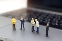 Miniatuurmensen: Zakenmanhanddruk aan bedrijfssucces Onli stock foto