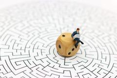 Miniatuurmensen: Zakenmanlezing op centrum van labyrint Concept royalty-vrije stock afbeelding