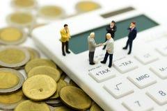 Miniatuurmensen: Zakenmantribune op calculator, maandelijks van de berekeningsbelasting/jaarlijks Beeldgebruik voor Belastingsber stock foto's