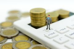 Miniatuurmensen: Zakenmantribune op calculator, maandelijks van de berekeningsbelasting/jaarlijks Beeldgebruik voor Belastingsber royalty-vrije stock foto