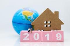 Miniatuurmensen: Zakenmanzitting op houten blok 2019 Beeldgebruik voor bedrijfsconcept royalty-vrije stock foto's