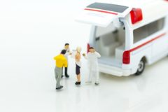 Miniatuurmensen: ziekenwagen voor behandeling van patiënten verre van medische faciliteiten Beeldgebruik voor Gezondheidszorgconc royalty-vrije stock foto's