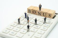 Miniatuurmensenzakenlieden die op inkomenswinsten wachten van de zaken om een bonus te betalen het gebruiken als achtergrond bedr stock afbeelding