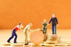 Miniatuurmensenzakenman die zich op geld bevinden royalty-vrije stock fotografie