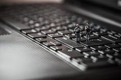 Miniatuurmepploeg die laptop computer beschermen Het concept van de technologie Stock Foto