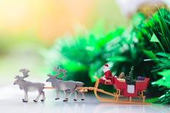 Miniatuursanta claus drijft een wagen met een rendier tijdens de sneeuwval Het gebruiken als concept in Kerstmisdag stock afbeelding
