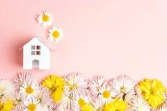 Miniatuurstuk speelgoed huis met bloemen en exemplaarspase op roze backgrou stock afbeeldingen
