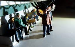 Miniatuurstuk speelgoed van mensen die van het werk aangaande een openbaar vervoerconcept reizen stock afbeeldingen