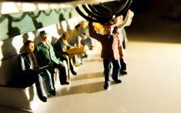 Miniatuurstuk speelgoed van mensen die van het werk aangaande een openbaar vervoerconcept reizen royalty-vrije stock afbeelding