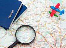 Miniatuurvliegtuig, paspoort en vergrootglas op kaart, reis rond de wereld Royalty-vrije Stock Foto