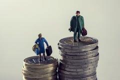 Miniatuurvrouw en man op stapels van euro muntstukken Stock Afbeelding
