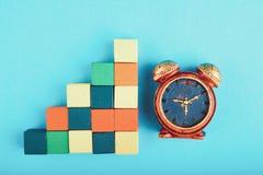 Miniatuurwekker en houten kubus op blauwe achtergrond royalty-vrije stock foto