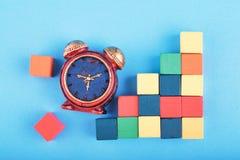 Miniatuurwekker en houten kubus op blauwe achtergrond stock foto's
