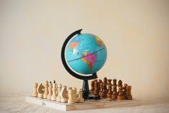 Miniatuurwereldbol model status op schaak houten raad Stock Afbeeldingen