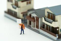 Miniatuurzakenlieden die de Huisvesting van de Investeringsanalyse bevinden zich of binnen royalty-vrije stock afbeeldingen