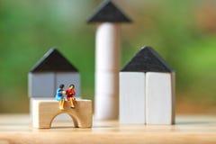 Miniatuurzakenlieden die op de houten Huisvesting of de investering van de Investeringsanalyse in roerende goederen zitten het ge stock afbeeldingen
