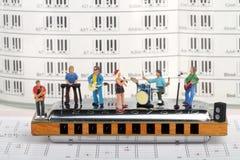 Miniatyr av en rockband som spelar på munspelet Royaltyfri Bild