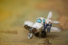 Miniatyr och flygplan med worldmap genom att använda som bakgrund Conc Arkivfoto