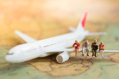 Miniatyraffärsfolk: väntande på flygplan för affärslag med kopieringsutrymme för lopp runt om världen, lopp för affärstur royaltyfri fotografi