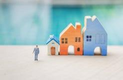 Miniatyraffärsman med det suddiga miniatyrhuset över suddig simbassängbakgrund Royaltyfri Fotografi