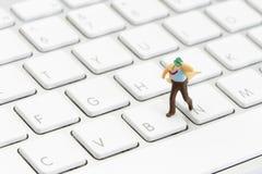 Miniatyraffärsman på ett tangentbord Arkivfoto