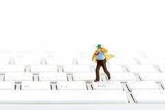Miniatyraffärsman på ett tangentbord Arkivbild
