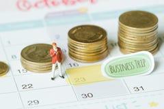 Miniatyraffärsman på kalender med buntmynt genom att använda som bakgrundsförpliktelse royaltyfri fotografi