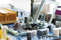 Miniatyrarbetare som reparerar en processor Royaltyfri Fotografi
