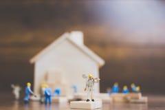 Miniatyrarbetarlagbyggande ett trähus Arkivfoto