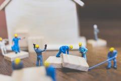 Miniatyrarbetarlagbyggande ett trähus Arkivbilder