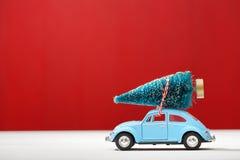 Miniatyrbil som bär en julgran fotografering för bildbyråer