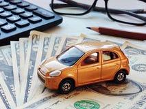 Miniatyrbok eller bokföringsunderlag för bilmodell-, räknemaskin-, dollarpengar- och besparingkonto på tabellen för kontorsskrivb Fotografering för Bildbyråer