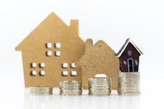 Miniatyrbyggande: Hus som vilar med bunten av mynt Bildbruk intecknar och fastighetsinvesteringen arkivbild