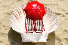 Miniatyrdeckchairs på stranden Arkivfoto