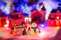 Miniatyrfestlig röd bakgrund, sagalandskap med den hållande stjärnan för snögubbe Julbegrepp, royaltyfri bild