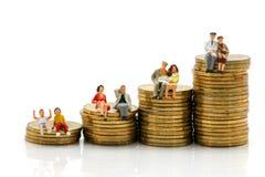 Miniatyrfolk: Åtskilligt åldersammanträde på bunten av mynt, affär fotografering för bildbyråer