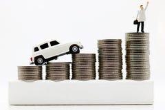 Miniatyrfolk: Affärsmän överst av myntpengar med bilen royaltyfri fotografi
