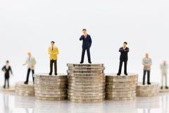 Miniatyrfolk: Affärsmananseende på bunt av mynt Bildbruk för skillnad i jobbposition av affären Arkivbild