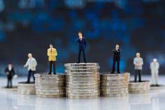 Miniatyrfolk: Affärsmananseende på bunt av mynt Bildbruk för skillnad i jobbposition av affären Royaltyfria Bilder