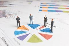Miniatyrfolk: Affärsmananseende på ett pappers- grafdiagram Arkivbilder