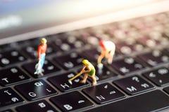 Miniatyrfolk: arbetarlag med knappen på en datorkeyboa arkivbilder