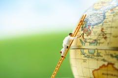 Miniatyrfolk: arbetarmålarfärg en världskarta, sparar världsconcen Royaltyfri Foto