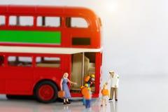 Miniatyrfolk, barn som får på schoolbusen med läraren royaltyfria foton